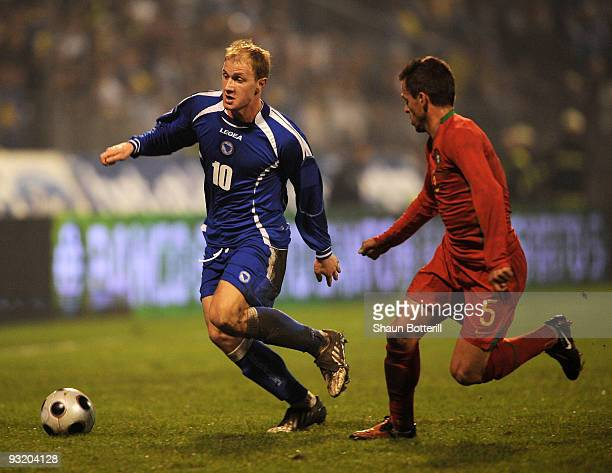 Senijad Ibricic of BosniaHerzegovina is challenged by Duda of Portugal during the FIFA2010 World Cup Qualifier 2nd Leg match between...