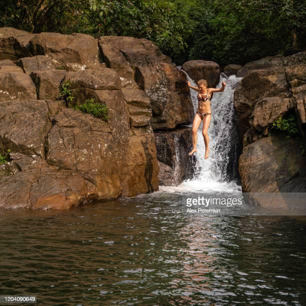 mujer activa de 55 años de edad saltando de las rocas a un pequeño lago en la cascada de polgampola (thambadola ella), sri lanka. - 50-59 years and women only fotografías e imágenes de stock
