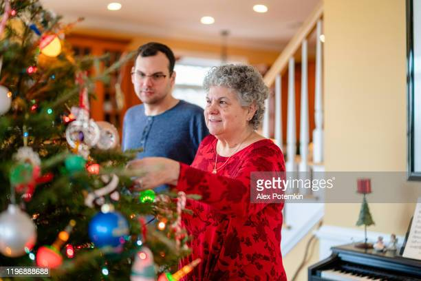 senior 65-years-old woman decorating christmas tree together with her adult son - 65 69 years stock pictures, royalty-free photos & images
