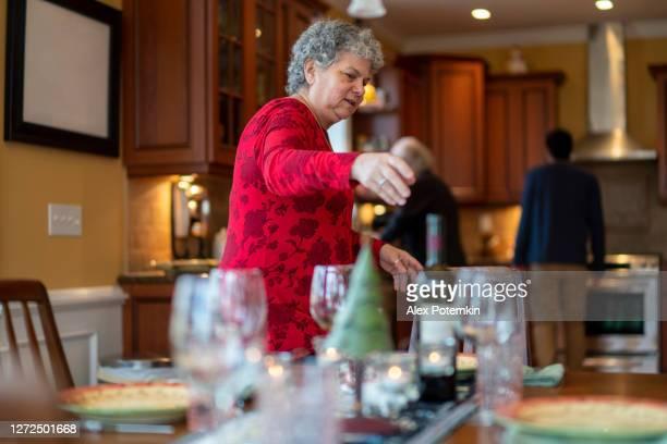 senior 65-jährige frau legt den tisch für die familie weihnachtstreffen urlaub abendessen, und der rest der familie hilft in der kulisse. - 30 34 years stock-fotos und bilder
