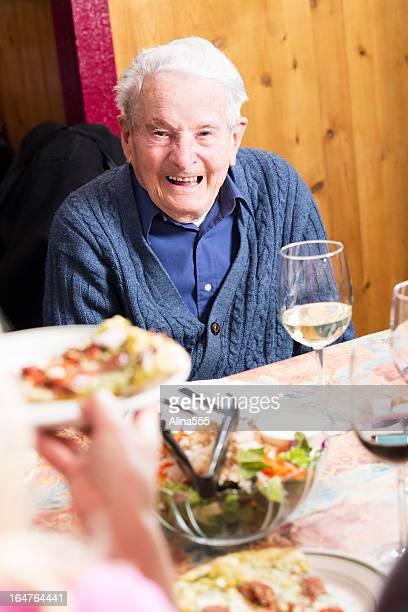 Senior 90-year old man laughing at pizza restaurant