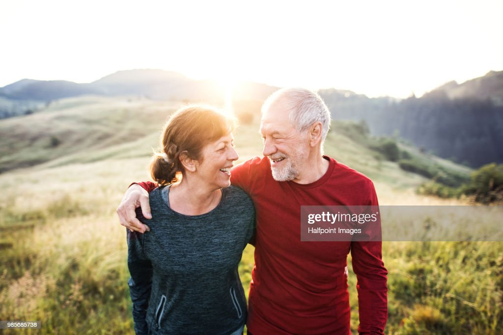 Senior active couple standing outdoors in nature in the foggy morning. : Stock-Foto
