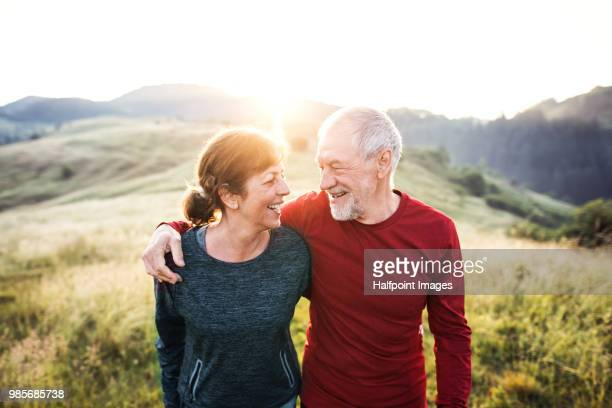 senior active couple standing outdoors in nature in the foggy morning. - actieve ouderen stockfoto's en -beelden