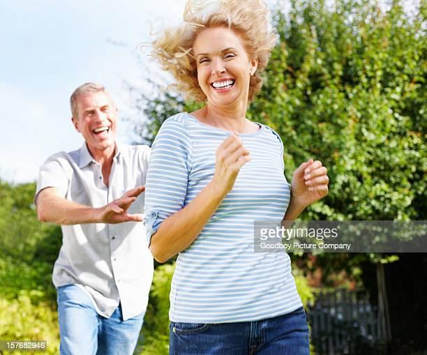 Senior active man running behind mature woman
