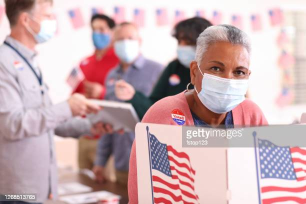 senior adult, african descent woman votes in usa election wearing mask. - voting stock pictures, royalty-free photos & images
