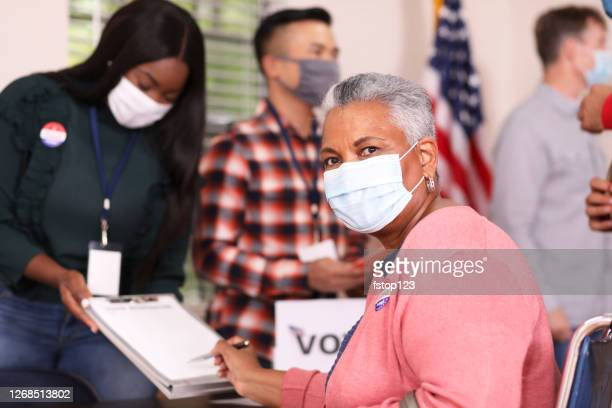 senior adult, african descent woman votes in usa election wearing mask. - polling station stock pictures, royalty-free photos & images