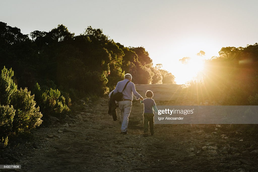 Senior adult and little boy walking on the road of Itatiaia National Park, Brazil : Stock Photo