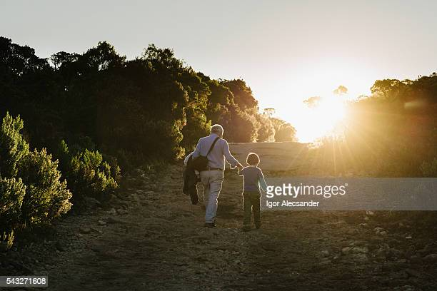 Senior adult and little boy walking on the road of Itatiaia National Park, Brazil