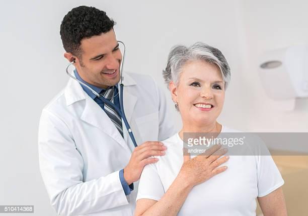 senior adult at the doctor - cardiólogo fotografías e imágenes de stock