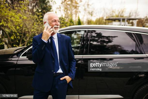 senior adult businessman talking on the phone - prestige car stock pictures, royalty-free photos & images