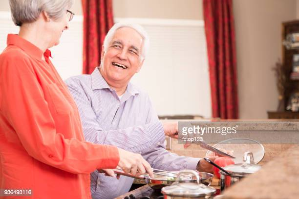 Senior adult couple at home cooking.