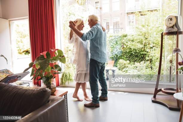 hoger volwassen paar in een romantisch ogenblik thuis, dat naast het venster aan de tuin danst - dancing stockfoto's en -beelden