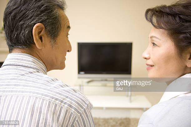 A Senior Adult Couple Looking at Each Other in a Living Room with a Television, Rear View, Side View, Differential Focus