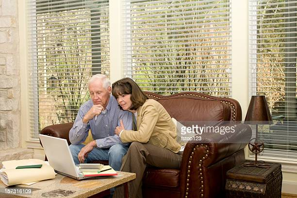 Senior adult couple studying the laptop computer results. Investments, bills.