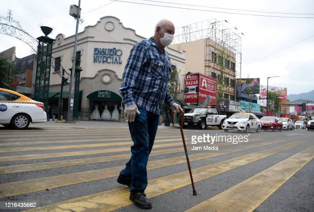 Senior adult crossing Avenida Juarez in downtown Monterrey wearing a face mask as a preventive measurement against the spread of Coronavirus on April...