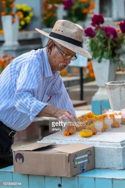 Senior adulte décorant une tombe sur le Día de los Muertos, Oaxaca
