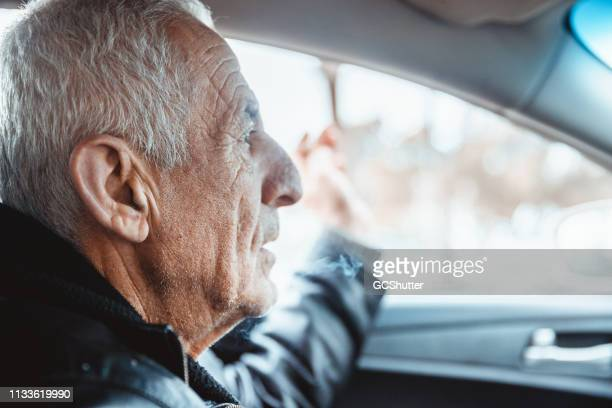 senior adult driving a car - arab old man stock pictures, royalty-free photos & images