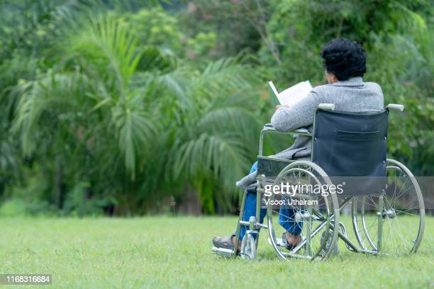 senior adult elderly asian women sit on wheelchair and reading book. - literature stock pictures, royalty-free photos & images