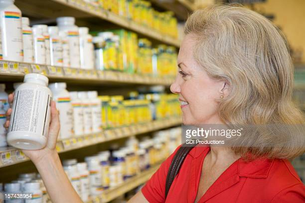 Senior Adult Female Reading Contents of Vitamin Bottle