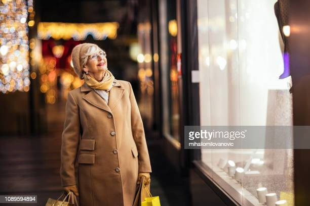 senior adult female shopping - one senior woman only stock pictures, royalty-free photos & images