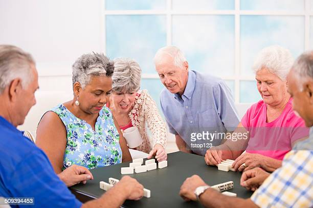 senior adult friends playing dominoes. home or community center setting. - community centre stock pictures, royalty-free photos & images