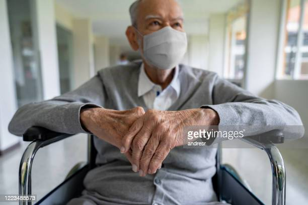 senior adult in a wheelchair at the hospital wearing a facemask - hospice stock pictures, royalty-free photos & images