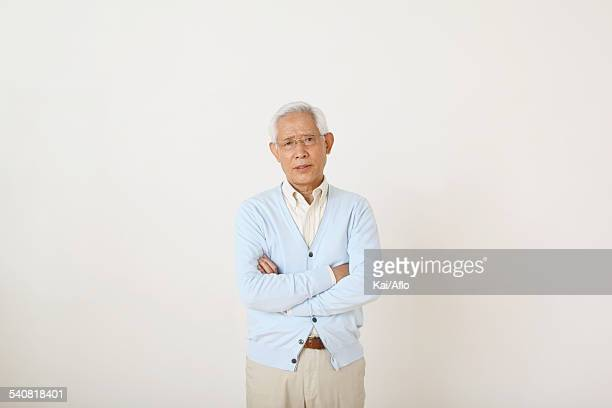 Senior adult Japanese man against white wall