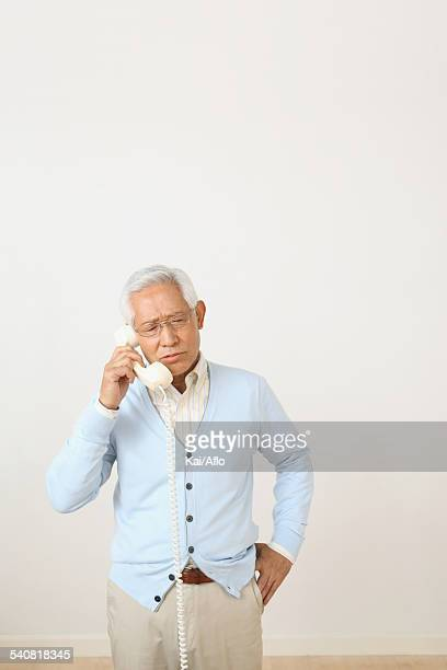 Senior adult Japanese man with phone against white wall