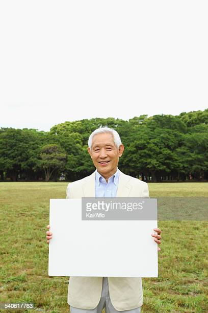 Senior adult Japanese man with whiteboard in a park