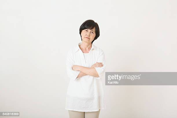 Senior adult Japanese woman against white wall