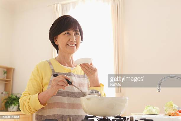 Senior adult Japanese woman cooking