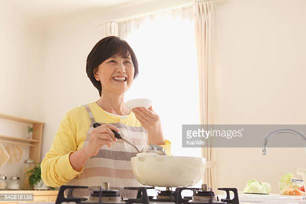 Senior adult Japanese woman cooking