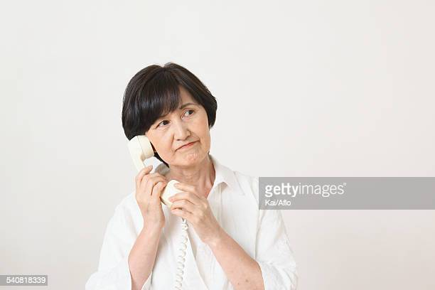 Senior adult Japanese woman with phone against white wall