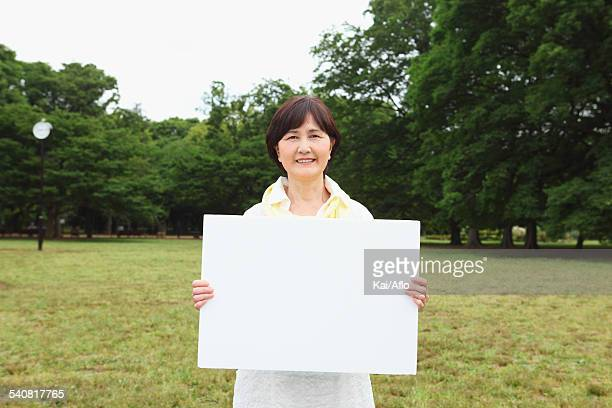Senior adult Japanese woman with whiteboard in a park