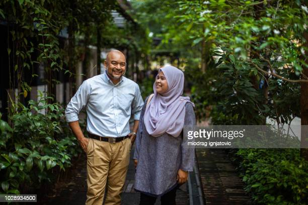 senior adult man and malaysian woman wearing hijab havig fun - mid adult stock pictures, royalty-free photos & images