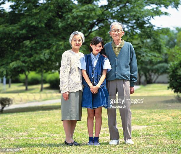 Senior adult man and woman standing together with a granddaughter, Front View