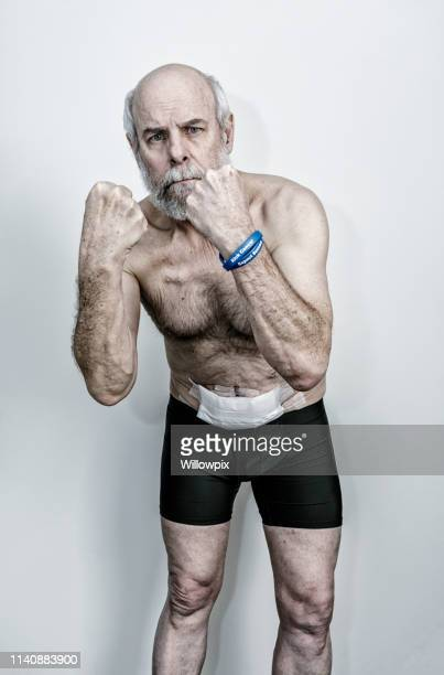 senior adult man boxer und colorectal cancer survivor - darmkrebs stock-fotos und bilder
