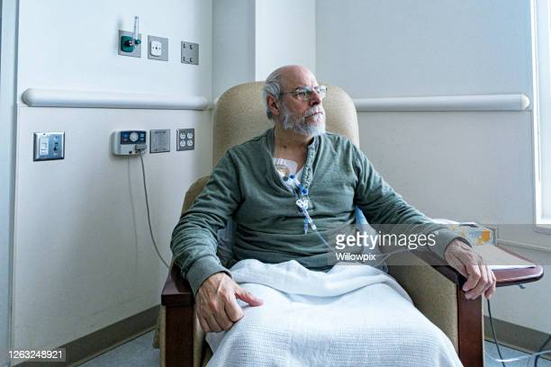 senior adult man cancer outpatient during chemotherapy iv infusion - colorectal cancer stock pictures, royalty-free photos & images