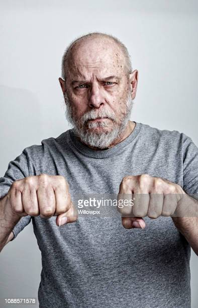 senior adult man chemotherapy patient making symbolic fists to fight cancer - lentigo stock pictures, royalty-free photos & images