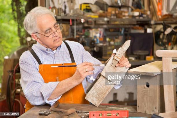 senior adult man restores antique furniture. - bird house stock photos and pictures