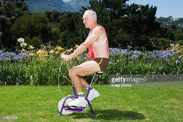 Senior adult man riding exercise bike