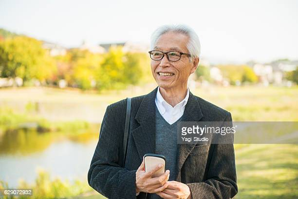 senior adult man using smart phone - japanese old man stock pictures, royalty-free photos & images