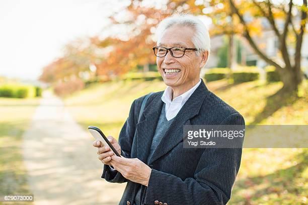 スマートフォンを使用したシニアアダルト男性 - 60代 ストックフォトと画像