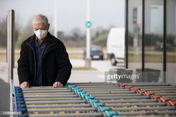 senior adult man wearing protective face mask when visiting supermarket - stock photo - italy coronavirus stock pictures, royalty-free photos & images