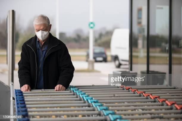 senior adult man wearing protective face mask when visiting supermarket - stock photo - maschera di protezione da lavoro foto e immagini stock