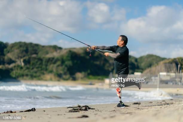 ビーチで人工脚釣りを持つシニア大人の男性 - 身体障害 ストックフォトと画像