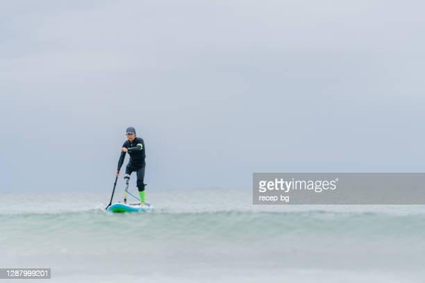senior adult man with artificial leg paddleboarding in sea - human leg stock pictures, royalty-free photos & images