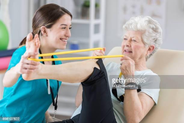 Senior erwachsenen Patienten lächelt mit ihr Arzt als She-Übungen