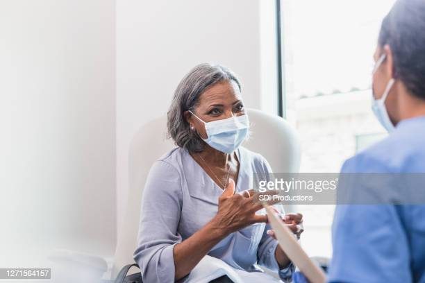 senior adult patient talks with doctor - vulnerability stock pictures, royalty-free photos & images