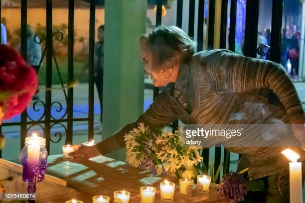 Senior adulte placer une bougie sur une tombe sur le Día de los Muertos, Oaxaca